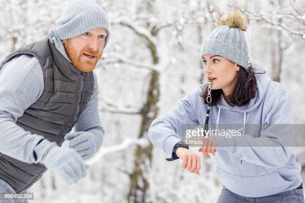 beautiful brunette feminine athletic woman training outdoors with redhead personal trainer in the snowy countryside - winter sports event stock pictures, royalty-free photos & images