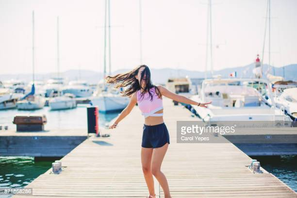 beautiful brunette girl dancing in a yacht harbor - saint tropez fotografías e imágenes de stock