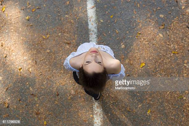 Beautiful brunette girl looking high up. Directly above view.