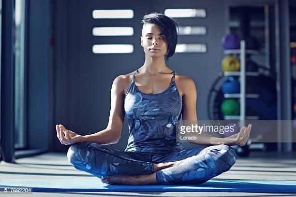 beautiful brunette woman in yoga position at gym - lotuspositie stockfoto's en -beelden
