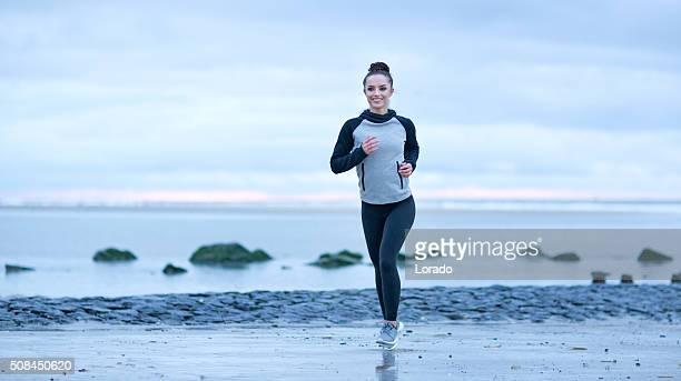Schöne Brünette Frau am Strand trägt Sport Kleidung