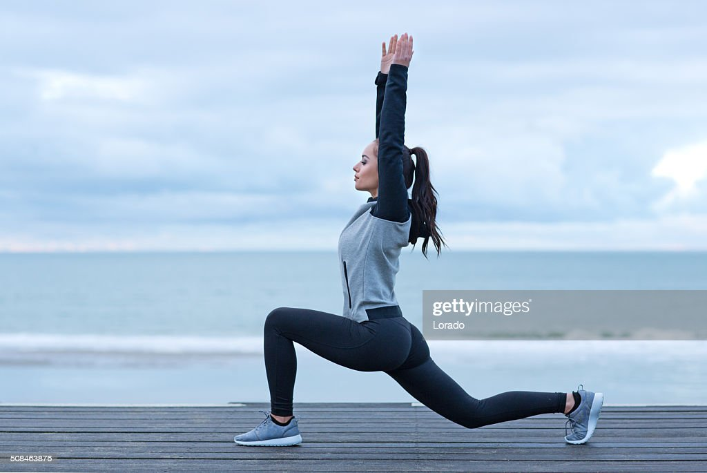 Beautiful brunette woman on a seafront wearing sports clothes : Stock Photo