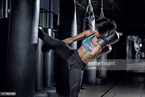 Beautiful brunette woman training during kickboxing workout at gym
