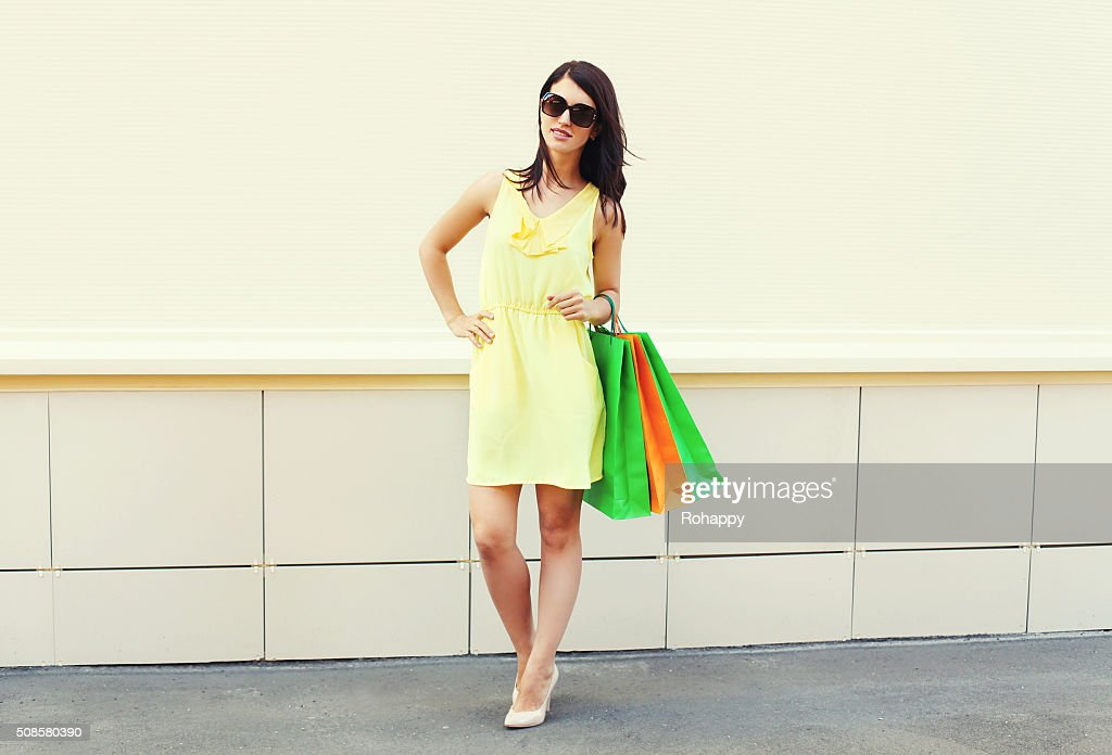 Beautiful brunette woman wearing dress with shopping bags in city : Stock Photo