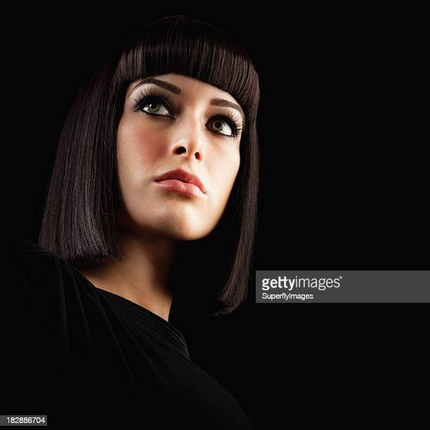 Beautiful Brunette Woman with Blunt Hairstyle on Black Background
