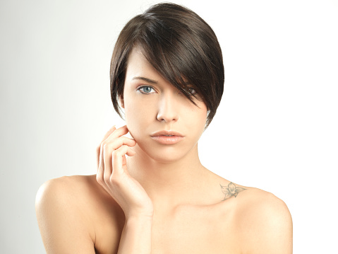 beautiful brunette woman with hand on face and short hair - gettyimageskorea