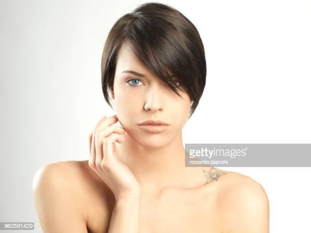 beautiful brunette woman with hand on face and short hair - kurzhaarschnitt stock-fotos und bilder