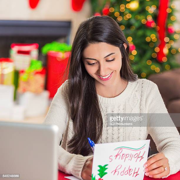 Beautiful brunette woman writing in a Christmas card