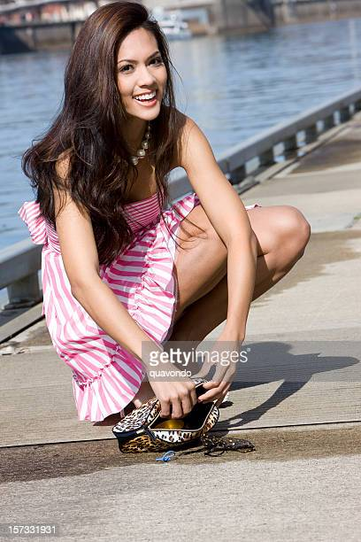 beautiful brunette young woman fashion model picking up purse outside - long purse stock photos and pictures