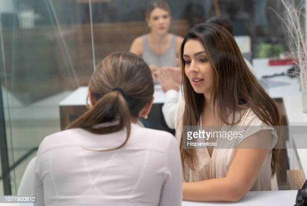 beautiful business female manager listening to a staff member at the office both sitting looking focused - hispanolistic stock photos and pictures
