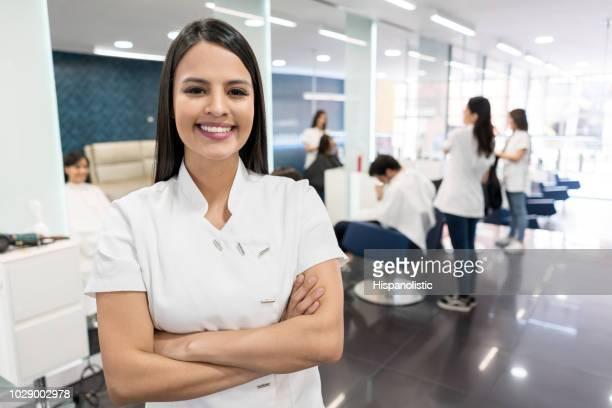 belle propriétaire d'un salon de coiffure en regardant caméra souriant avec les bras croisés et les visiteurs à la puisse tester fond une coupe de cheveux - salon de coiffure photos et images de collection