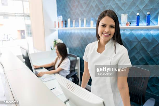 beautiful business owner of a hair salon standing behind the reception smiling at camera - beauty care occupation stock photos and pictures