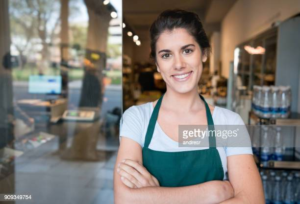 beautiful business owner with arms crossed standing at the entrance of her food shop - saleswoman stock photos and pictures