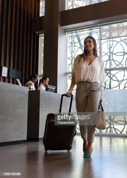 beautiful business woman checking into hotel walking towards room looking very happy - hotel stock pictures, royalty-free photos & images