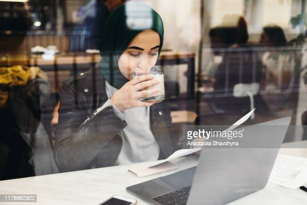 beautiful business woman in hijab working with laptop in cafe - islam stock pictures, royalty-free photos & images