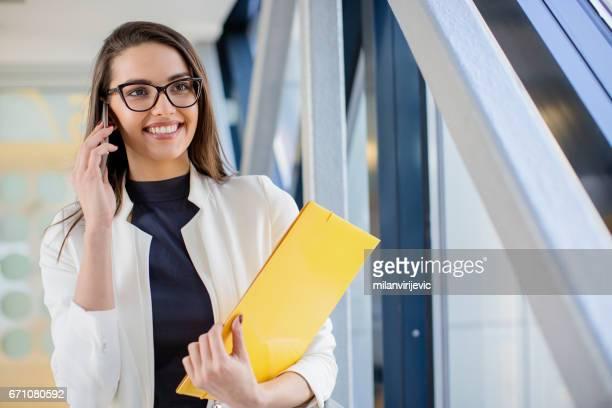 Schöne Geschäftsfrau Lächeln auf den Lippen und im Gespräch mit Handy