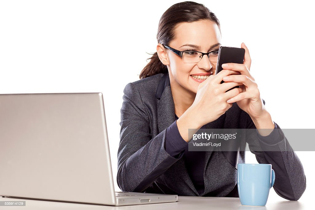 Beautiful business woman texting on the phone at her desk : Stock Photo