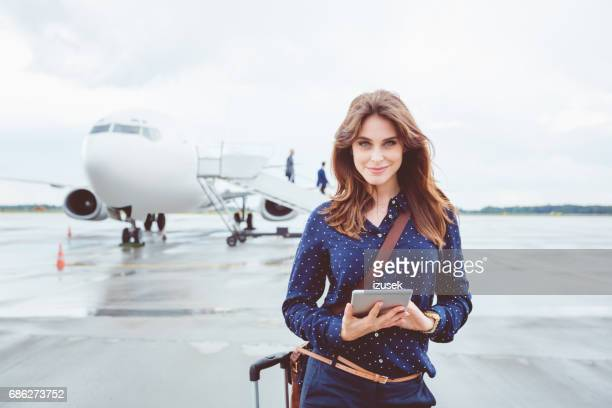 Beautiful business woman with digital tablet in front of airplane