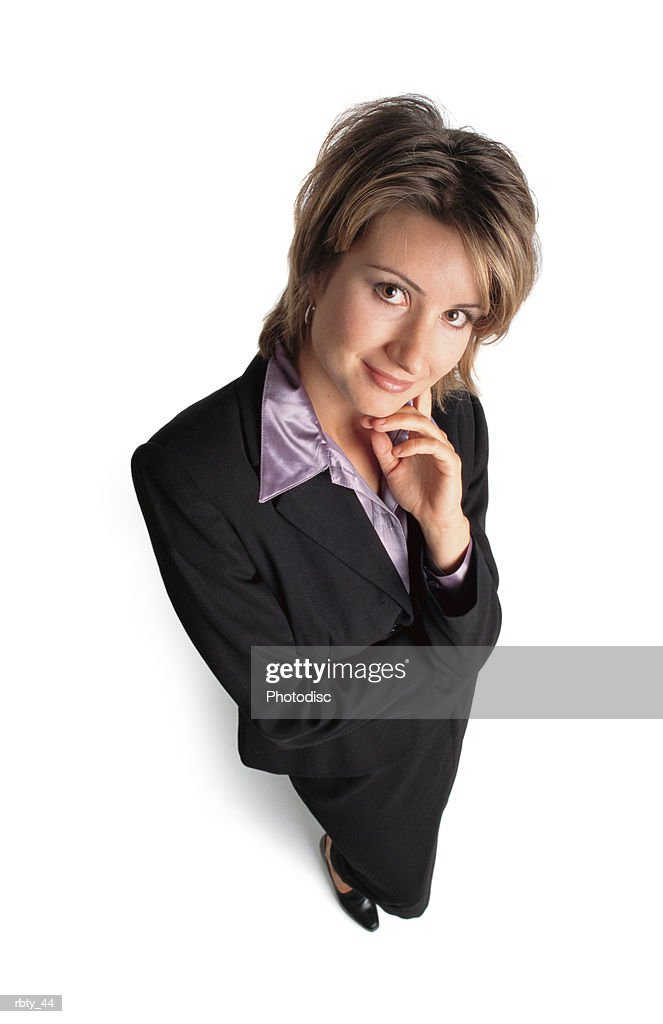 beautiful business woman with short brown hair wearing a purple shirt under a dark suit looks up at the camera and poses with one hand to her chin and smiles : Stockfoto