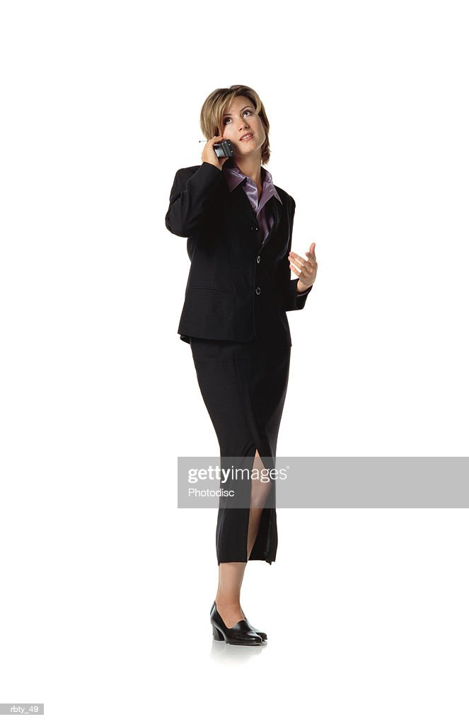 beautiful business woman with short brown hair wearing a purple silk shirt under a dark dress suit and skirt and black shoes talks into a cellular phone as she looks off into the distance : Foto de stock