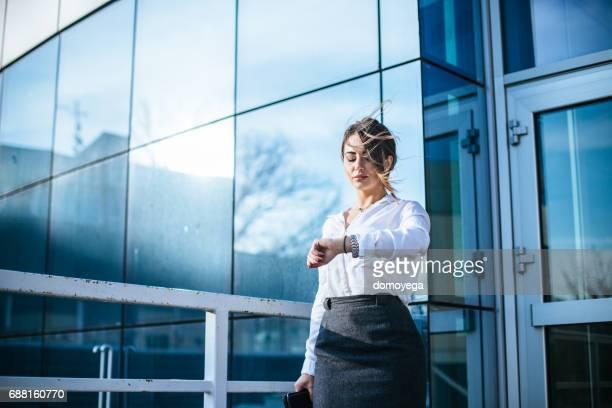Mooie zakenvrouw controleren de tijd voor het Bureau