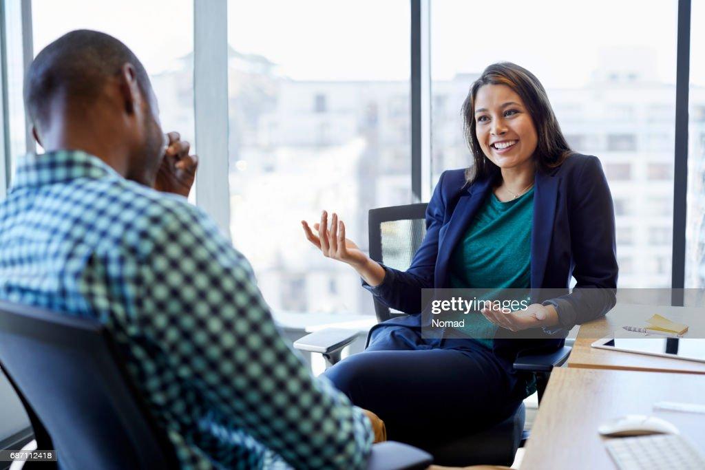 Bela empresária discutindo com o colega masculina no escritório criativo. Jovens executivos estão sentados em cadeiras contra a janela. Eles estão vestindo roupas normais inteligentes. : Foto de stock