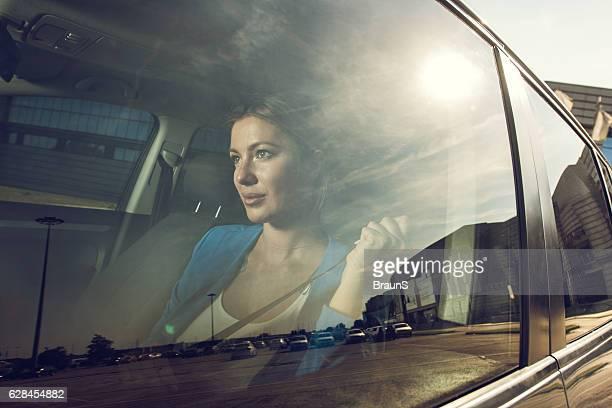 Beautiful businesswoman fastening seatbelt in a car.