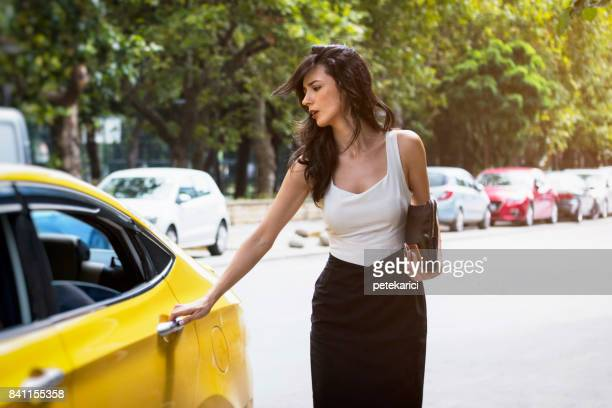 Beautiful businesswoman getting into yellow taxi