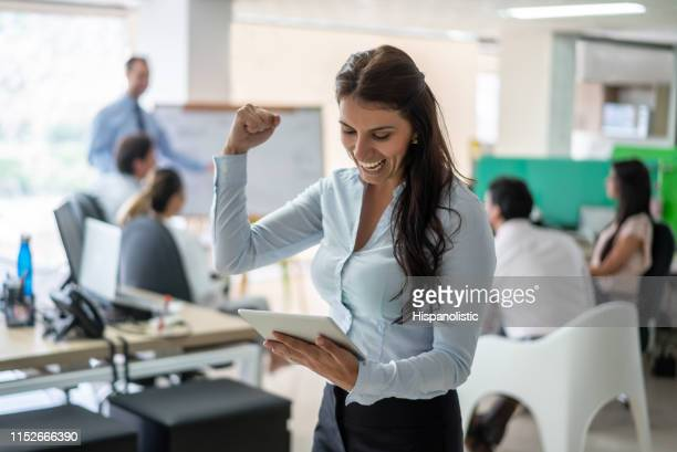 beautiful businesswoman looking at tablet celebrating very excited at the office - hispanolistic stock photos and pictures