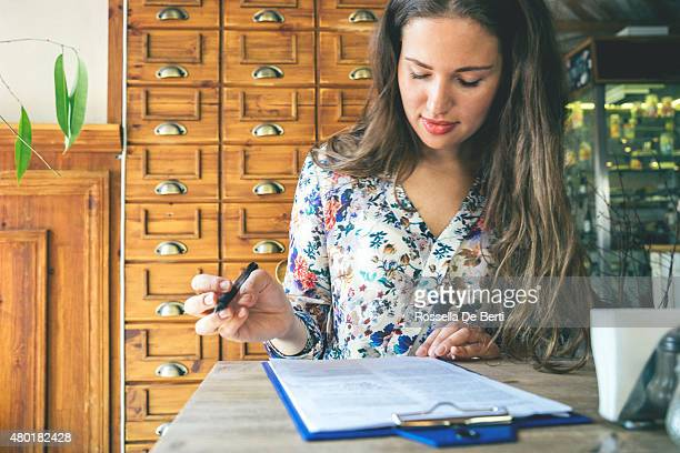 beautiful businesswoman signing contract in a cafe indoors - survey stock photos and pictures