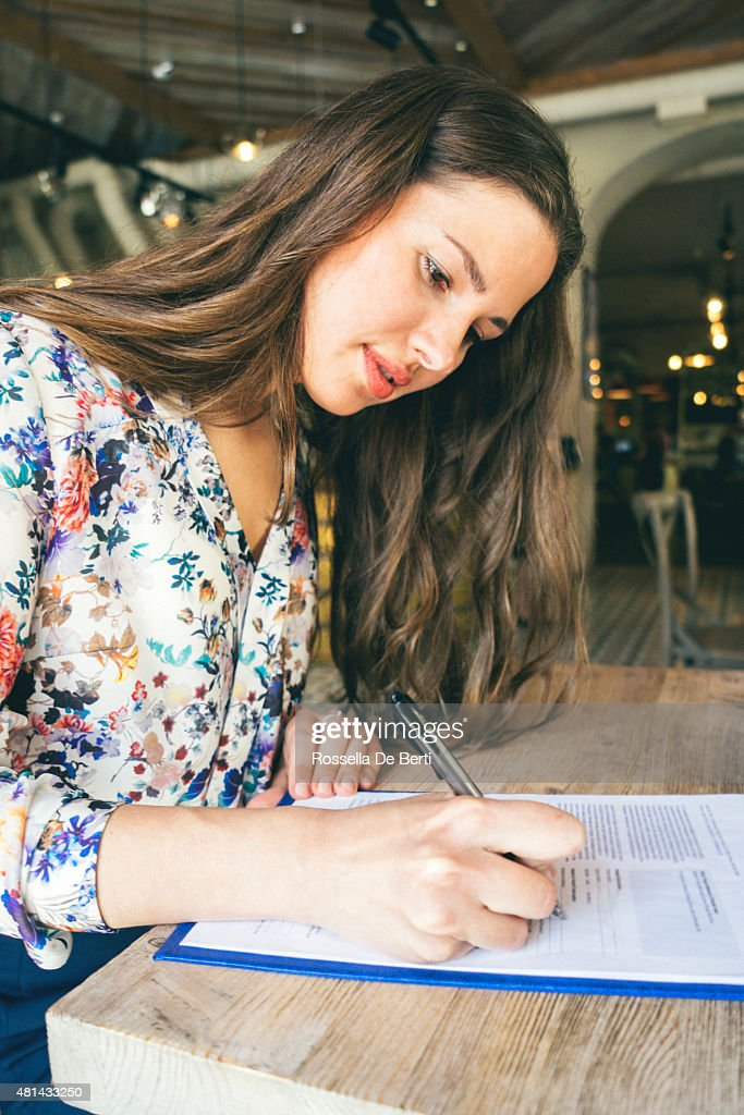 Beautiful Businesswoman Signing Contract In A Cafe Indoors : Stock Photo