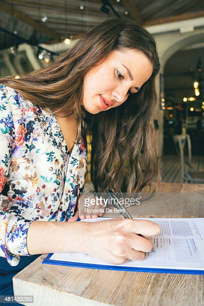 beautiful businesswoman signing contract in a cafe indoors - form filling stock pictures, royalty-free photos & images
