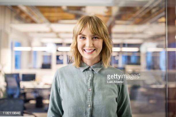 beautiful businesswoman standing in modern office. - smiling stock-fotos und bilder
