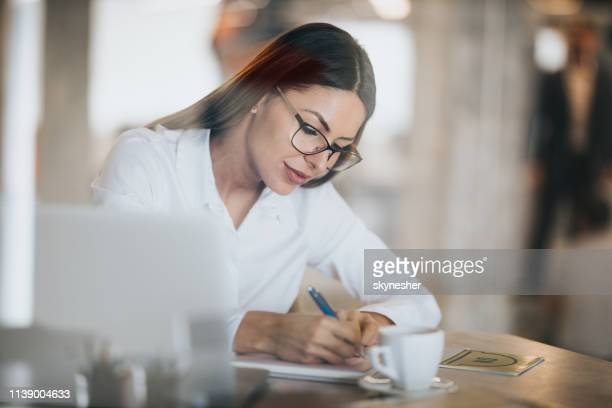beautiful businesswoman taking notes in the office. - economist stock pictures, royalty-free photos & images