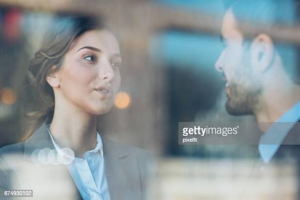 Schöne Geschäftsfrau im Gespräch mit einem Kollegen