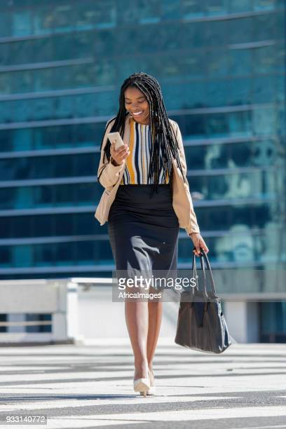 beautiful businesswoman texting on her mobile phone while talking through the city. - black purse stock pictures, royalty-free photos & images