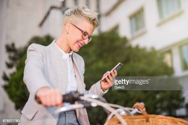 Beautiful businesswoman typing a message while sitting on her bicycle.