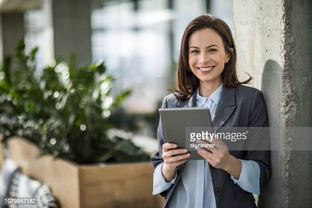 beautiful businesswoman using digital tablet in the office. - economist stock pictures, royalty-free photos & images