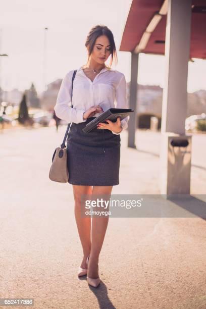デジタルタブレットを使用して、美しい屋外のビジネスウーマン - 若い女性一人 ストックフォトと画像