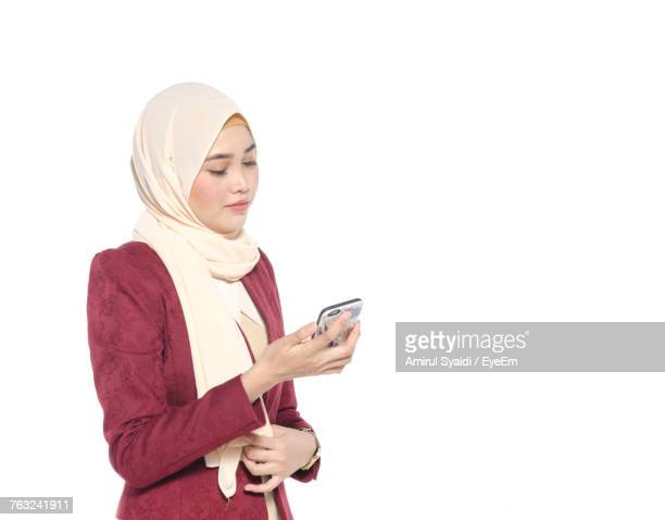 Beautiful Businesswoman Using Mobile Phone Against White Background