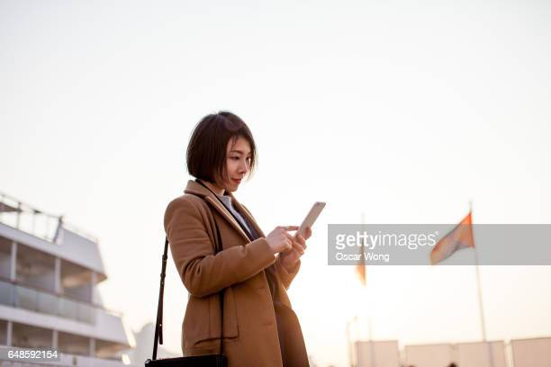 Beautiful businesswoman using smartphone next to a cruise