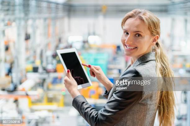 Beautiful businesswoman using touchpad at factory