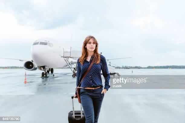 Schöne Geschäftsfrau zu Fuß vor Flugzeug am Flughafen