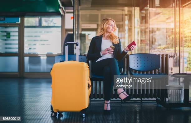 Beautiful businesswoman with suitcase sitting in airport waiting room with passport and using phone