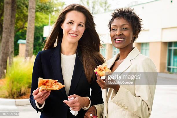 Wunderschöne Geschäftsfrauen Genießen Sie pizza-Mittagessen im Freien