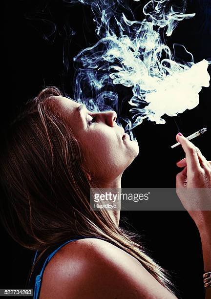 beautiful but stoned blonde puffing on marijuana reefer - smoking weed stock photos and pictures