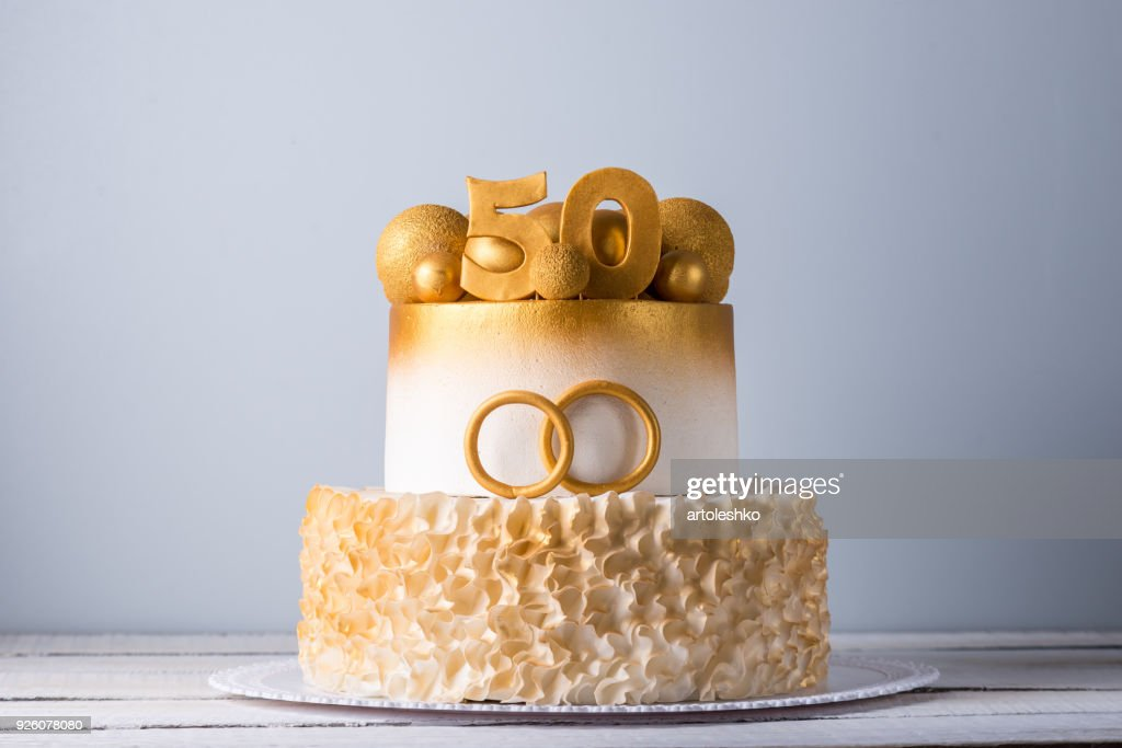 Beautiful cake for the 50th anniversary of the wedding decorated with gold balls and rings. Concept of festive desserts : Foto de stock