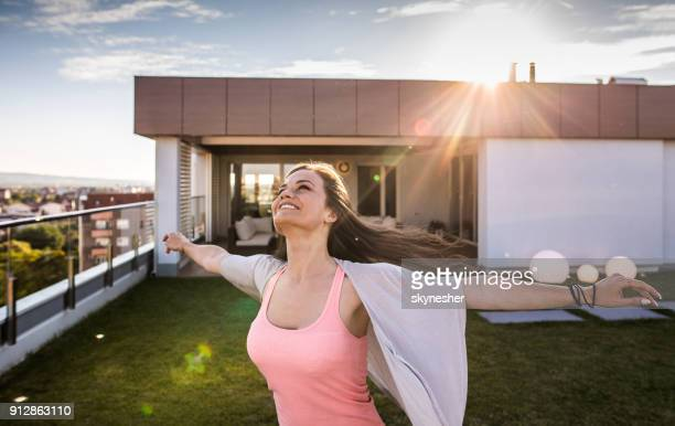 beautiful carefree woman having fun on a balcony in front of her penthouse. - women of penthouse stock photos and pictures