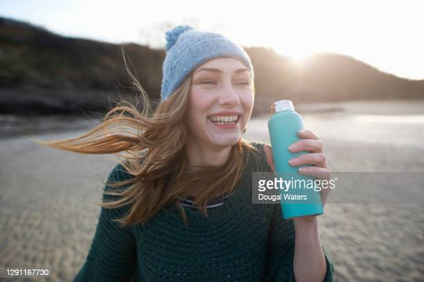 beautiful carefree woman on winter beach with green flask. - low tide stock pictures, royalty-free photos & images