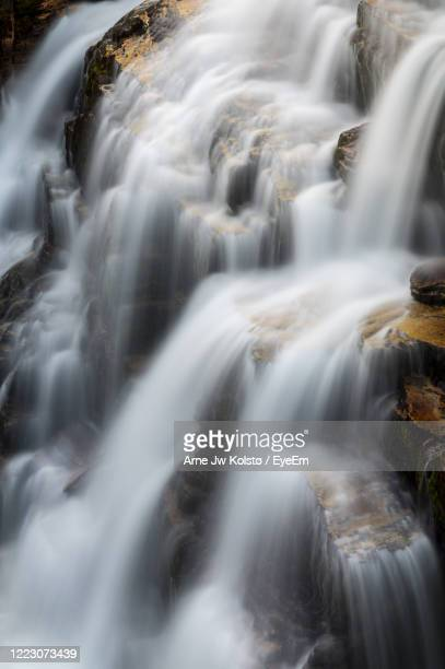 beautiful cascade of water flowing in a waterfall in nordic mountain area. - arne jw kolstø stock pictures, royalty-free photos & images